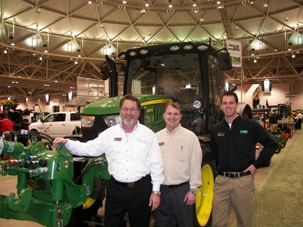 (L-R): John Braunshausen, Dan Scharber and Eric Brunelle, Scharber & Sons, Rogers Minn., showcased many pieces of equipment, like this John Deere 6125R.