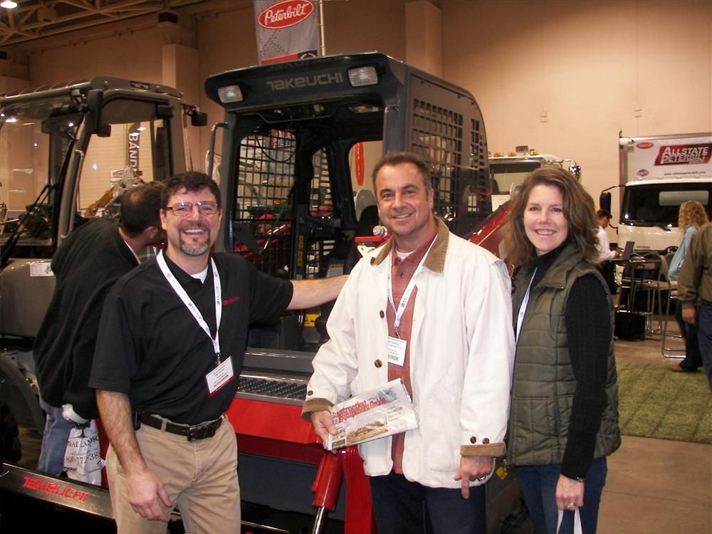 (L-R): Tim Rients, territory manager of Road Machinery & Supplies, Savage, Minn., shows Schifsky Landscaping Inc. owners Troy and Sheila Schifsky of Stillwater, Minn., the latest features of this Takeuchi TL10 track machine.