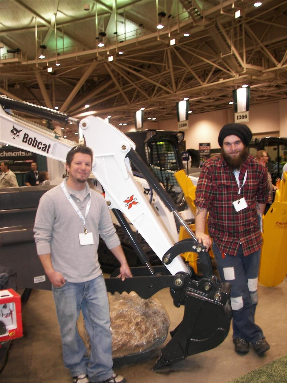 Isaak Smith (L) and Karl Poling, both of I. Smith Earthscapes, St. Paul, Minn., attempt to guess the weight of a boulder carried by this Bobcat E26 excavator. If they guess correctly, they win a toy Bobcat T190. Lano Equipment Inc. of Anoka, Minn., sponso