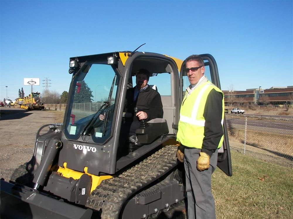 Dan Miller of Empire Bucket, Hudson, Wis., sits in a new Volvo MCT 125c track machine while Nuss Truck & Equipment's Scott Leseman, regional sales manager, points out all the new features.