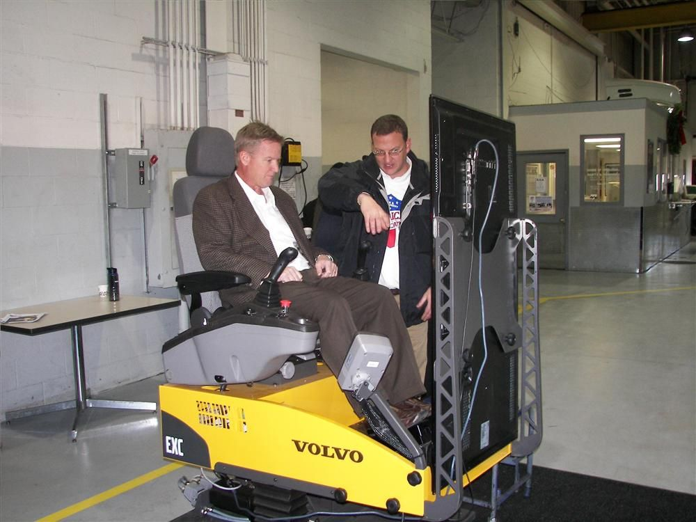 Timothy Trom (seated), vice president, finance and operations, Spray Control Systems, Byron, Minn., tries out the Volvo EX210 excavator simulator while Pete Stroh, Nuss Equipment, sales, SW territory, gives out some pointers.