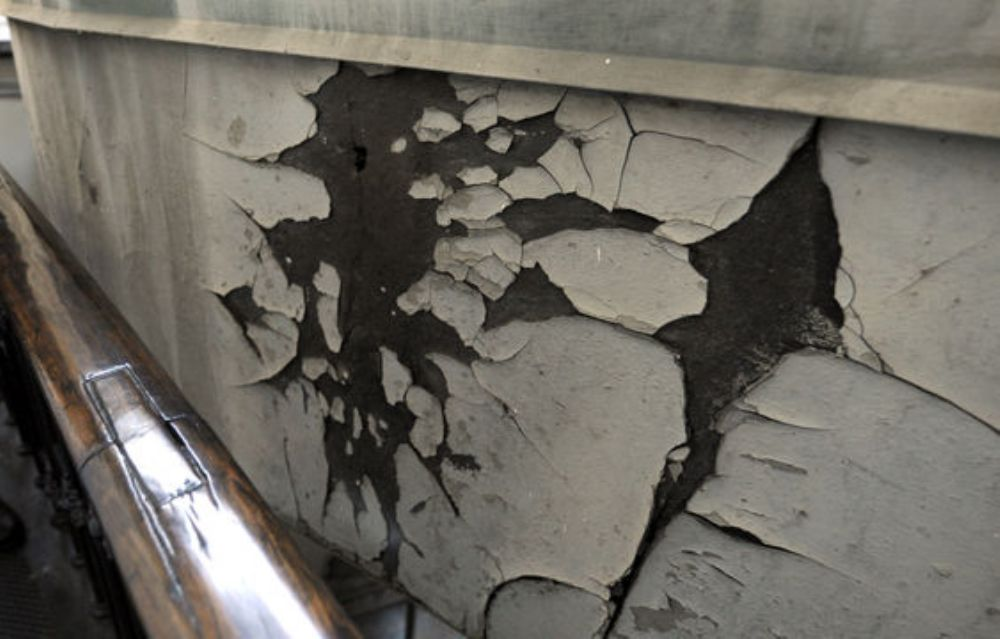 This Dec. 19, 2013, file photo shows cracked and peeling paint visible during a media tour of the Capitol dome on Capitol Hill in Washington. This world-famous symbol of democracy is going under cover, as workers start a two-year, $60 million renovation o