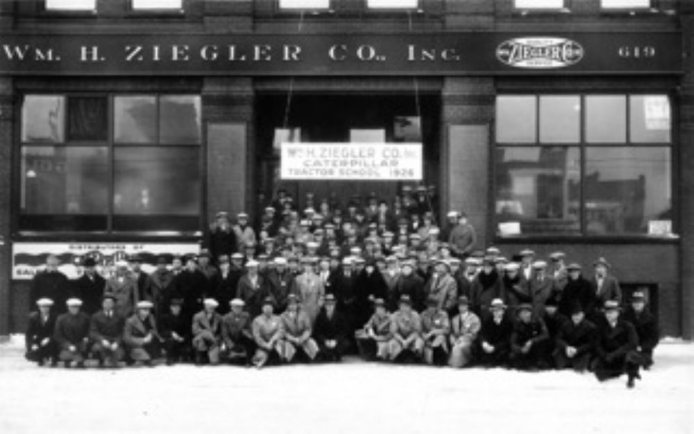 """Operators and servicemen received training in the care and operation of Caterpillar tractors at locally held """"Caterpillar schools."""" The William H. Ziegler Co. Inc. was an early promoter of these schools. This photo was taken in 1926 in front o"""