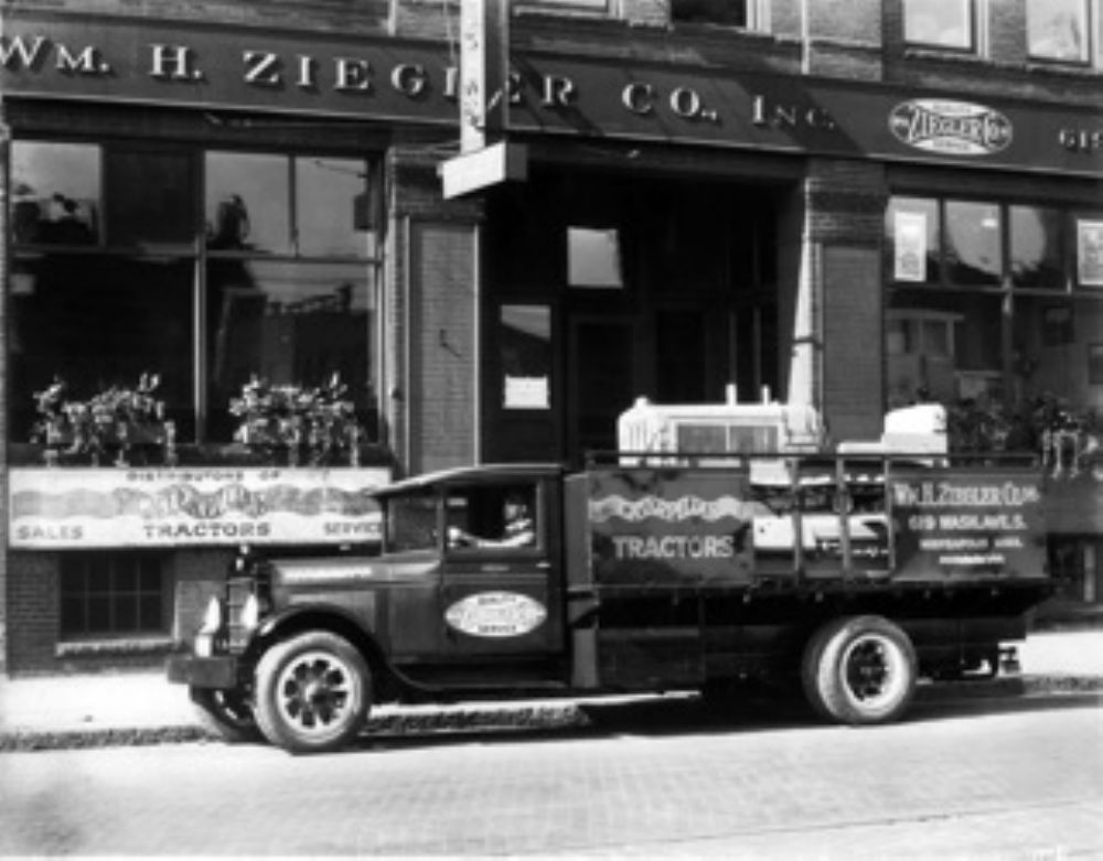 An REO truck hauling a Caterpillar Twenty tractor. The Twenty was the first tractor designed after the formation of the Caterpillar Tractor Co. in 1925 and went into production April 2nd, 1928.  Photo taken August 1928.