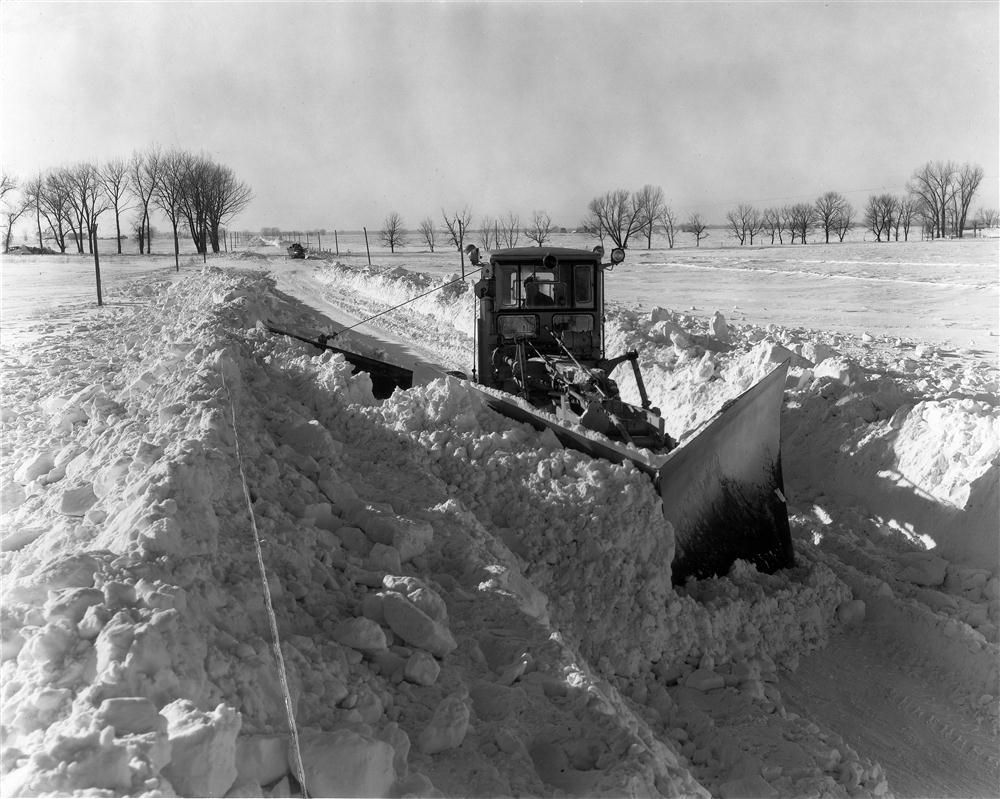 A Caterpillar No. 12 motorgrader with V plow and wings is shown clearing a Carver County, Minn., township road after a February 1952 snowstorm. Thinking it would be a good opportunity to demonstrate the 12's capabilities, Ziegler offered help with c