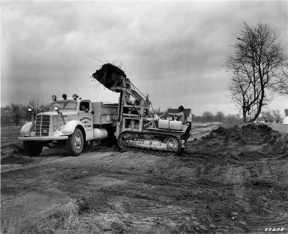 A Caterpillar diesel D4 tractor with a cable controlled Traxcavator loader widens streets in Richfield, Minn., in 1946. A city-owned Mack dump truck is used to haul away the fill. The D4 tractor/Traxcavator also was  used for stripping gravel pits, loadin