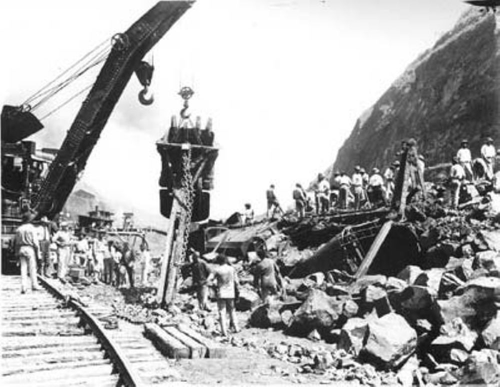 A crane removes dipper from steam shovel wrecked in a rock slide