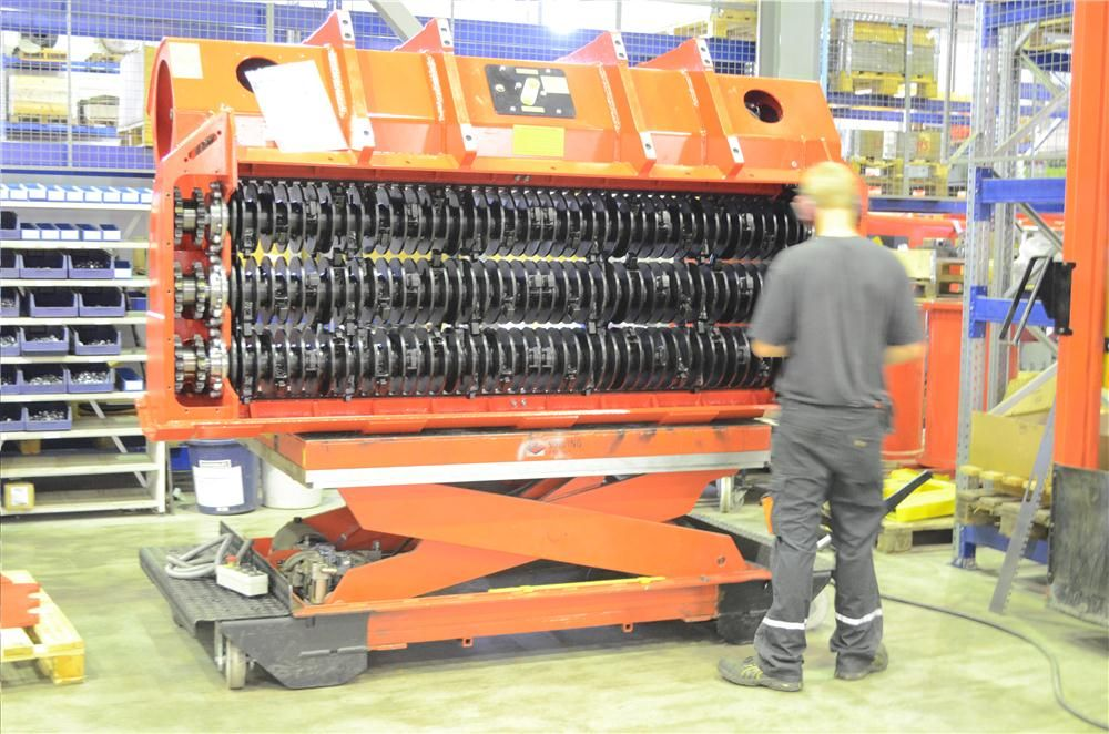 An ALLU worker installs blades on a Screener Crusher bucket at the company's headquarters in Finland.