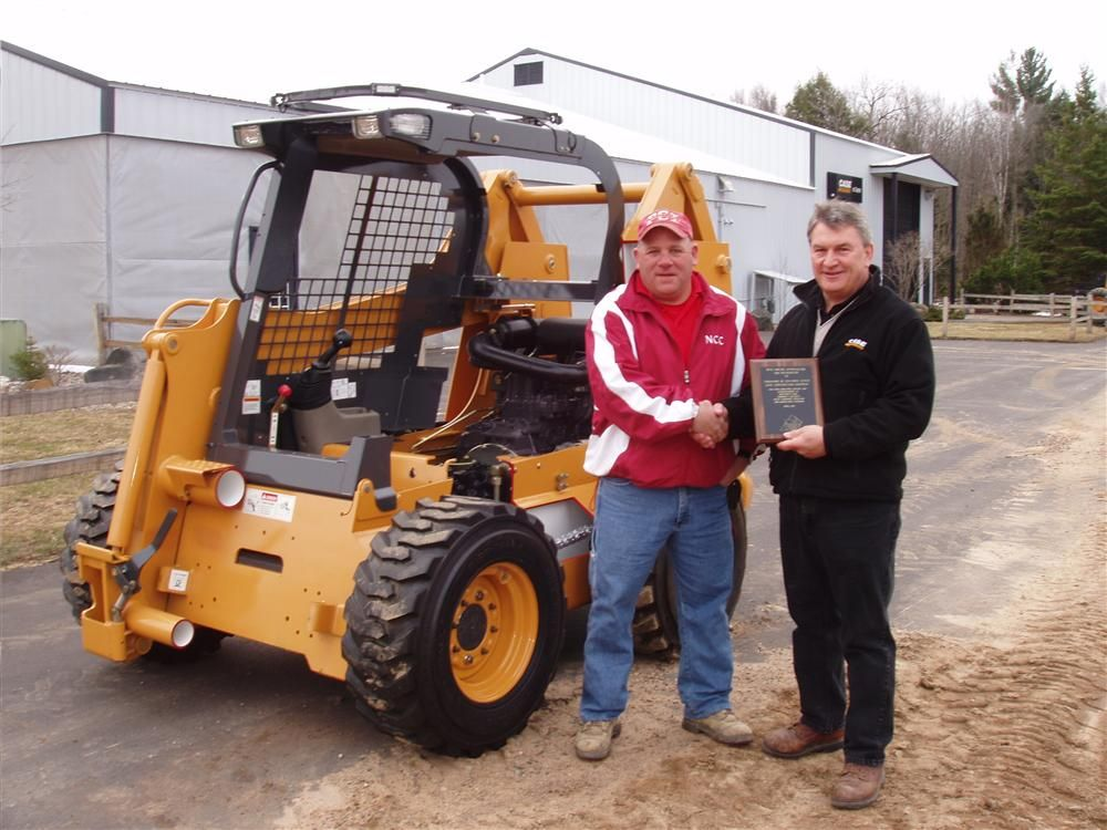 Roger Solberg (L), heavy equipment operations and maintenance instructor of Northwest Iowa Community College, accepts the donation of a cutaway training model of a Case skid steer loader while presenting a plaque of appreciation to Russ Wadzinski, general