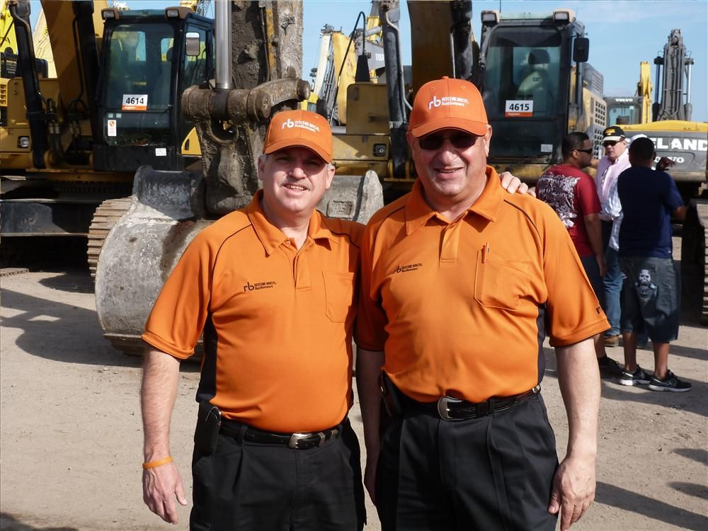 Fred Vilsmeier (L) and John Korrey, both of Ritchie Bros., ready themselves for their turn to call bids.