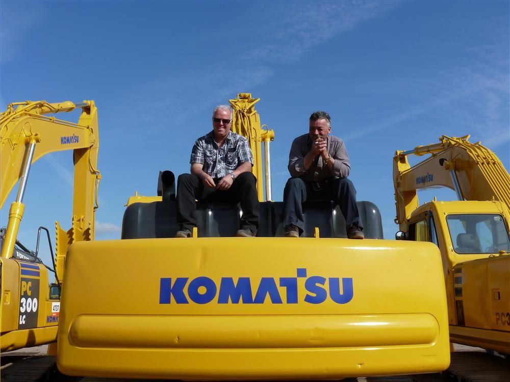 Michel Majean (L) and Michel Morin take in the bidding while atop a Komatsu hydraulic excavator.
