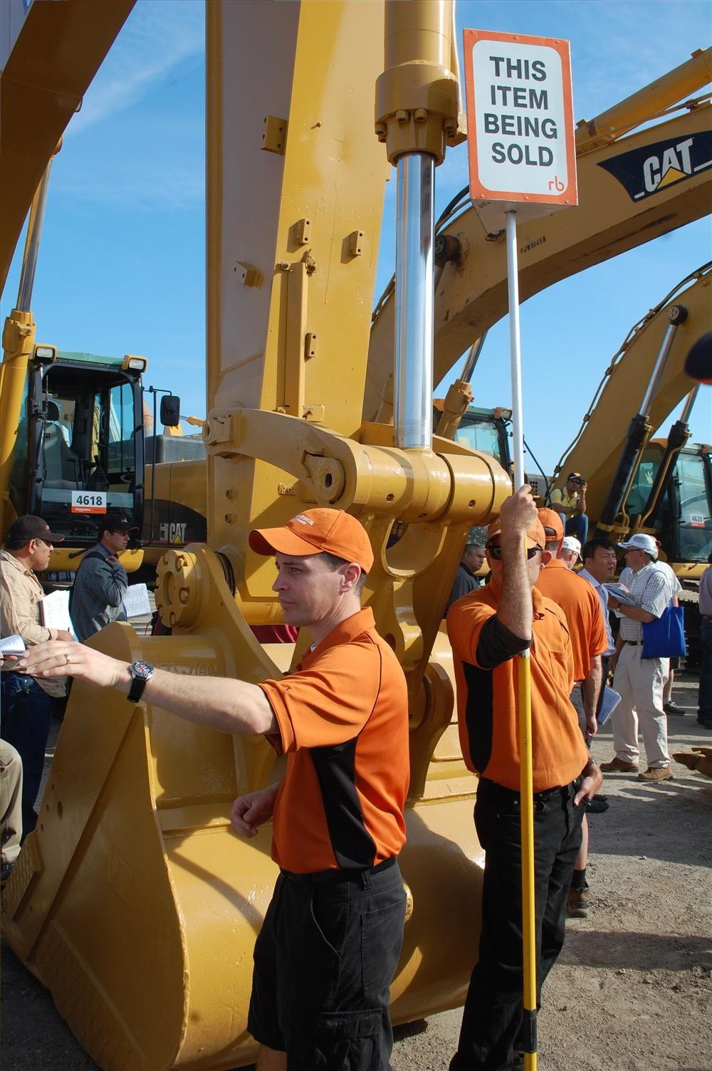 Excavator bidding keeps the ring men on their toes as they signal bids to the auctioneers.