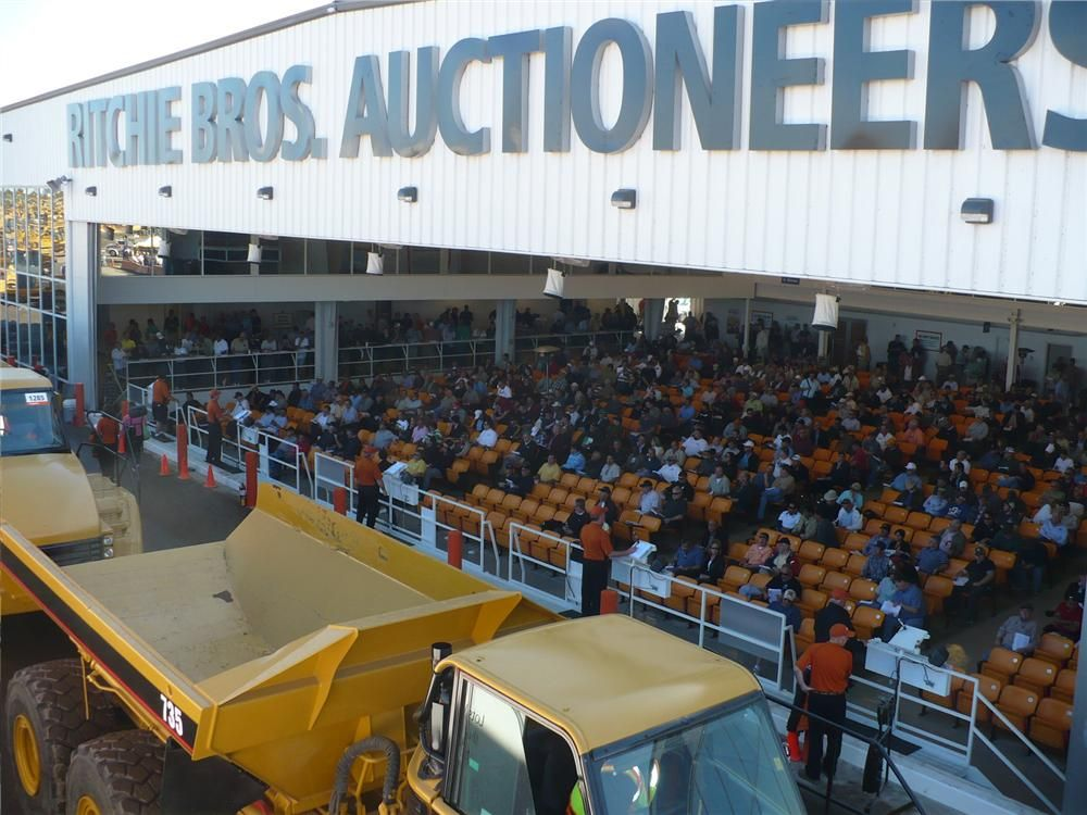 Caterpillar trucks roll across the ramp during Ritchie Bros.' auctions in Florida.