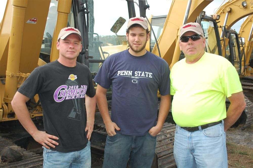 (L-R): Nick Bock, Mike Perry and Guy Harman from Erie, Pa., take a hard look at several of the excavators slated to be sold.