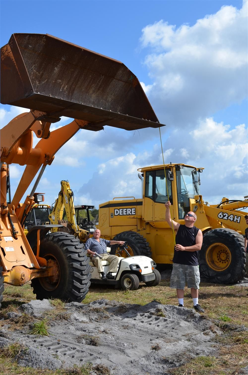 Larry Youngblood, owner and president of Youngblood Paving Inc., Wampum, Pa., measures the bucket height on this wheel loader.