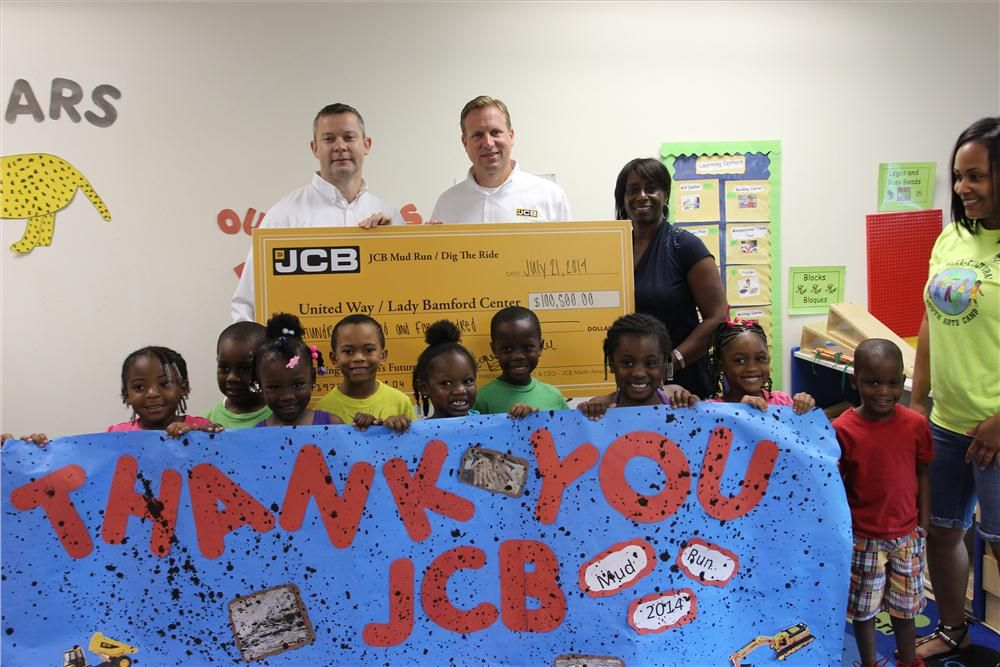 Steve Vernon, VP finance, JCB, and Thom Peebles, VP marketing, JCB, present a check for $100,500 — the proceeds from this year's Mud Run and Dig the Ride — to The Lady Bamford Center children staff and the Executive Director of Wesley Center,