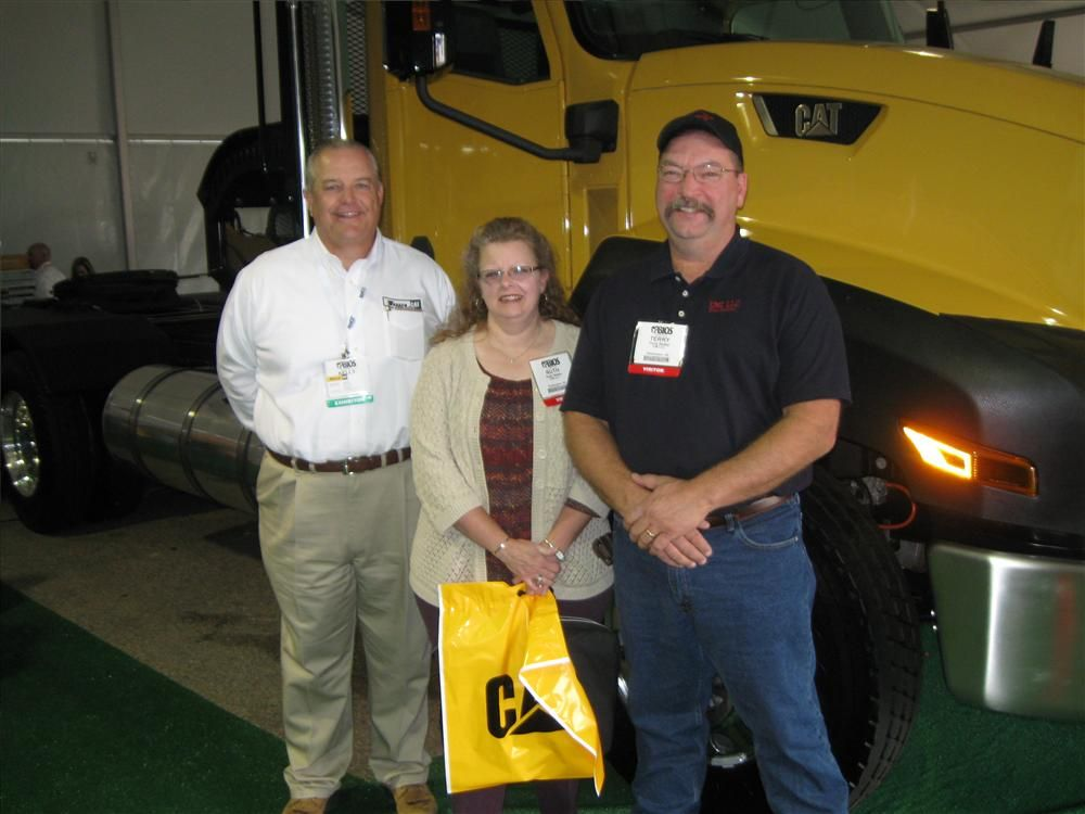 Kelly Kirkland (L) Warren CAT, Odessa, Texas, discusses the body system for this 475 hp (354 kW) Cat CT13 and a Cat CX 31 automatic transmission with the designer and fabricator, Terry Baily (center) of EMI Body Systems in Washington, Kan., and his wife R