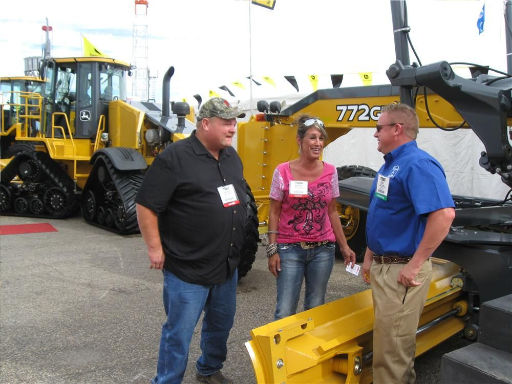 (L-R): Dewight Anderson and Wendy Clark of Total Truck & Trailer LLC in Norman, Okla., are learning a lot about John Deere equipment from Eric Schiel of Yellowhouse Machinery in Odessa, Texas.
