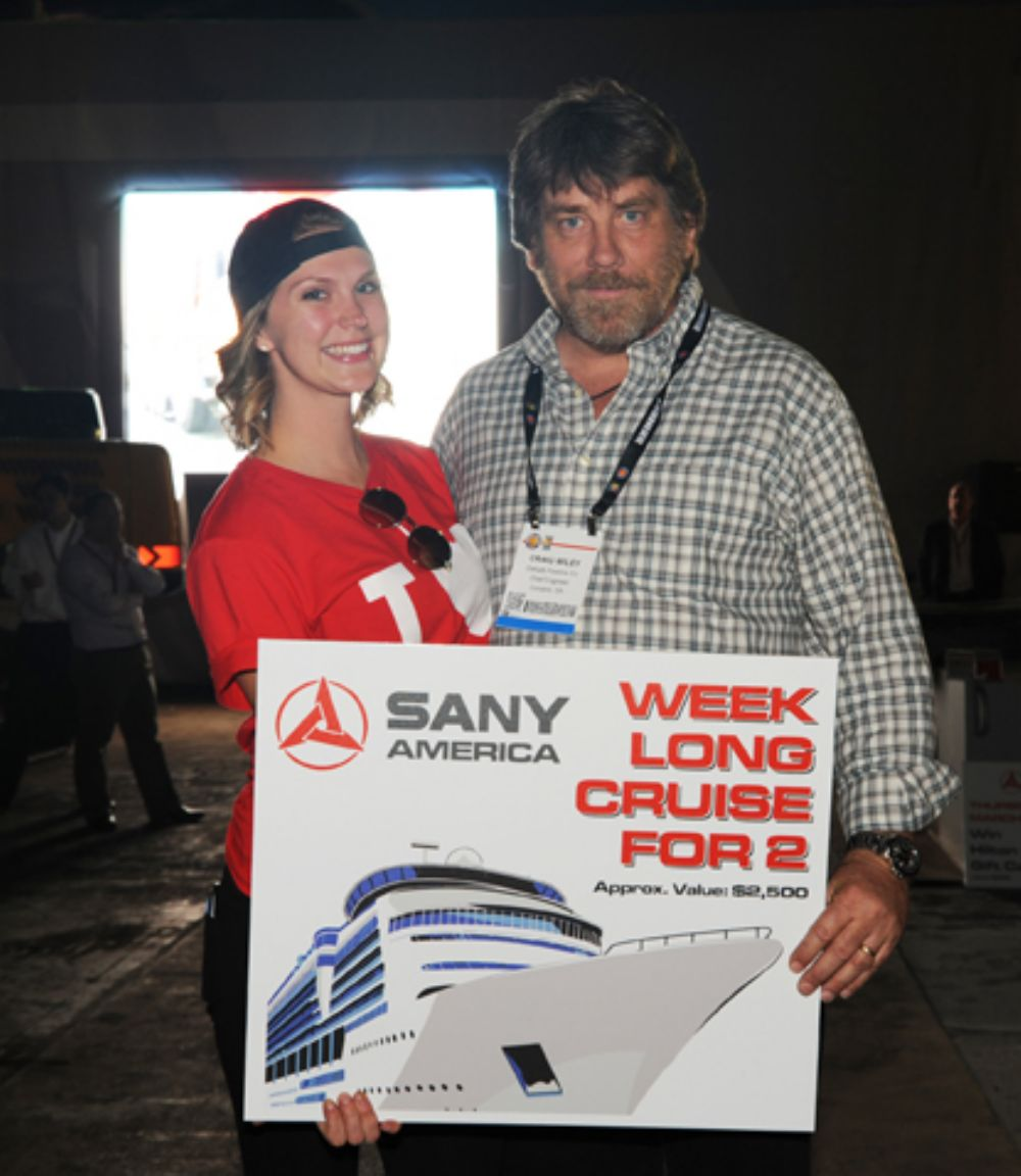 Craig Wiley of DeKalb Pipeline Co., Conyers, Ga., poses with a Sany America event hostess after winning a seven-day Caribbean cruise for two at a hospitality event for Sany customers and dealers.