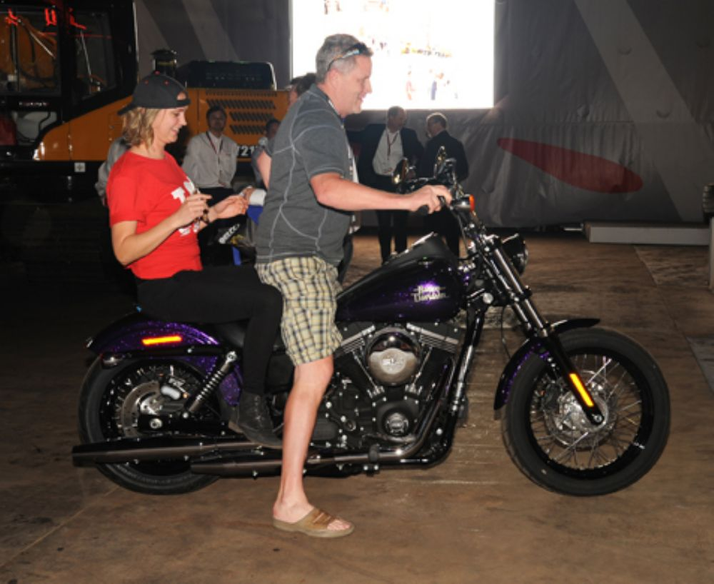 Bud Pecoy of Mid Country Machinery, Ft. Dodge, Iowa, is joined by a Sany hostess as he tries out the grand prize of a Harley-Davidson Street Bob motorcycle he received from Sany America at a hospitality event for Sany customers and dealers.