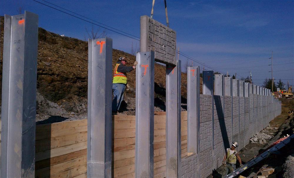 Crews place precast panels into the retaining wall.
