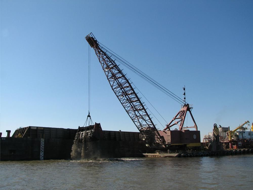 Stacy Ouellette/U.S. Army Corps of Engineers photo. A clamshell dredge moves dredged materials from the Chesapeake Bay into a scow for transport to Poplar Island.