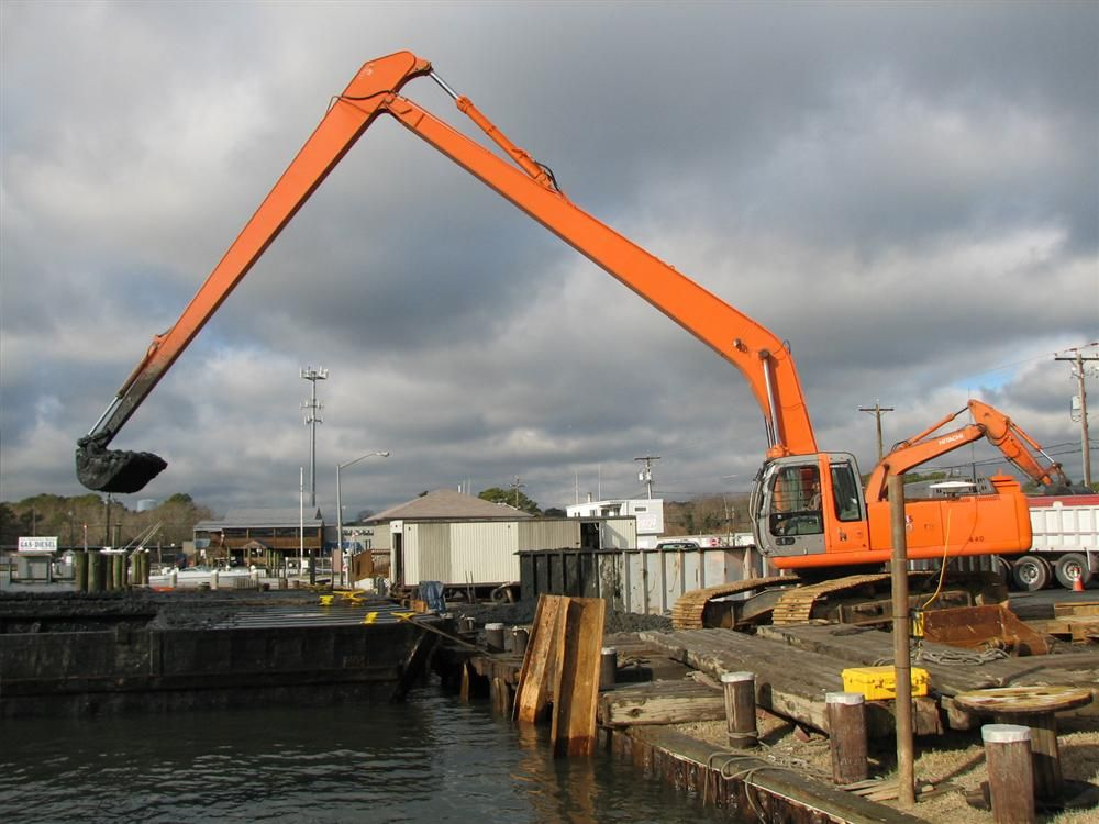 Stacy Ouellette/U.S. Army Corps of Engineers photo. A bucket dredge is used to move dredged material from a scow to a pick-up truck for transport to the placement site in Ocean City, Md.