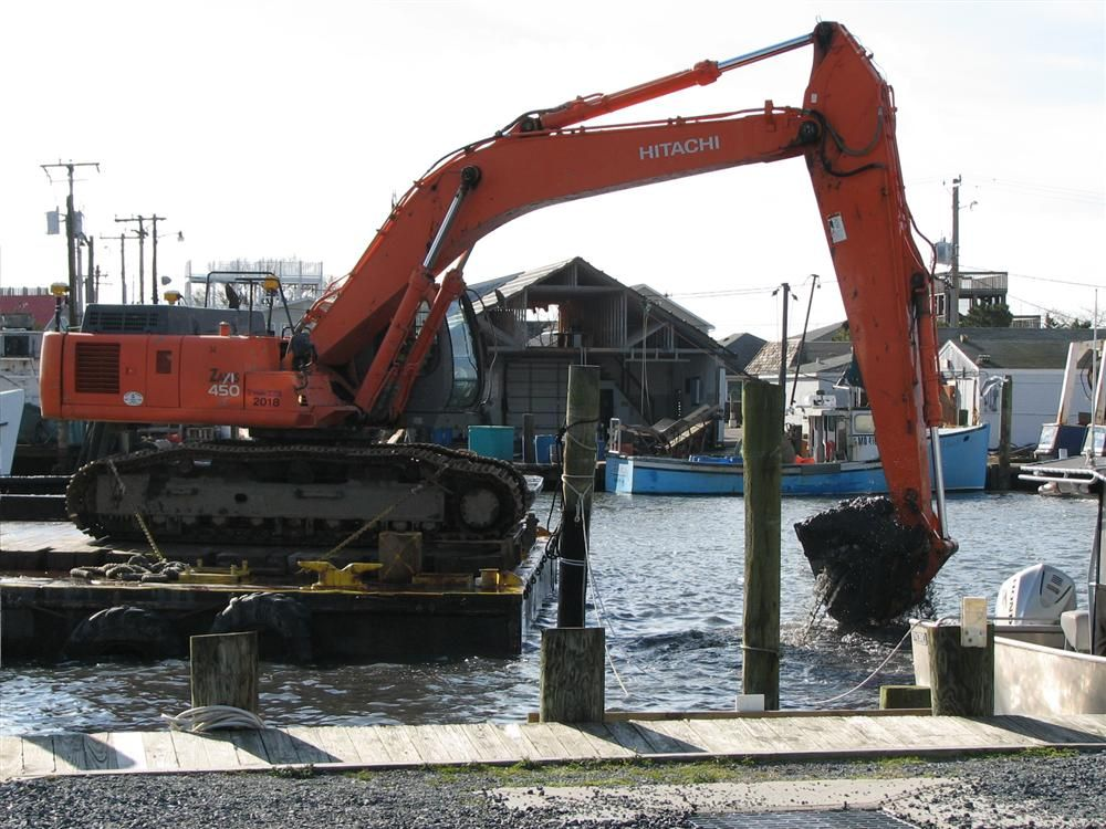 Stacy Ouellette/U.S. Army Corps of Engineers photo. A bucket dredge works to move dredged material to a scow for transport to the placement site.