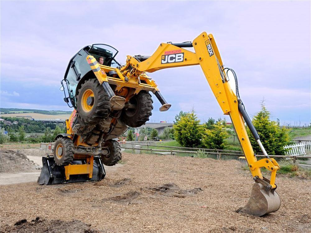 DiggerlandUSA.com photo The stunt team shows off their skills in this JCB 3CX excavator.
