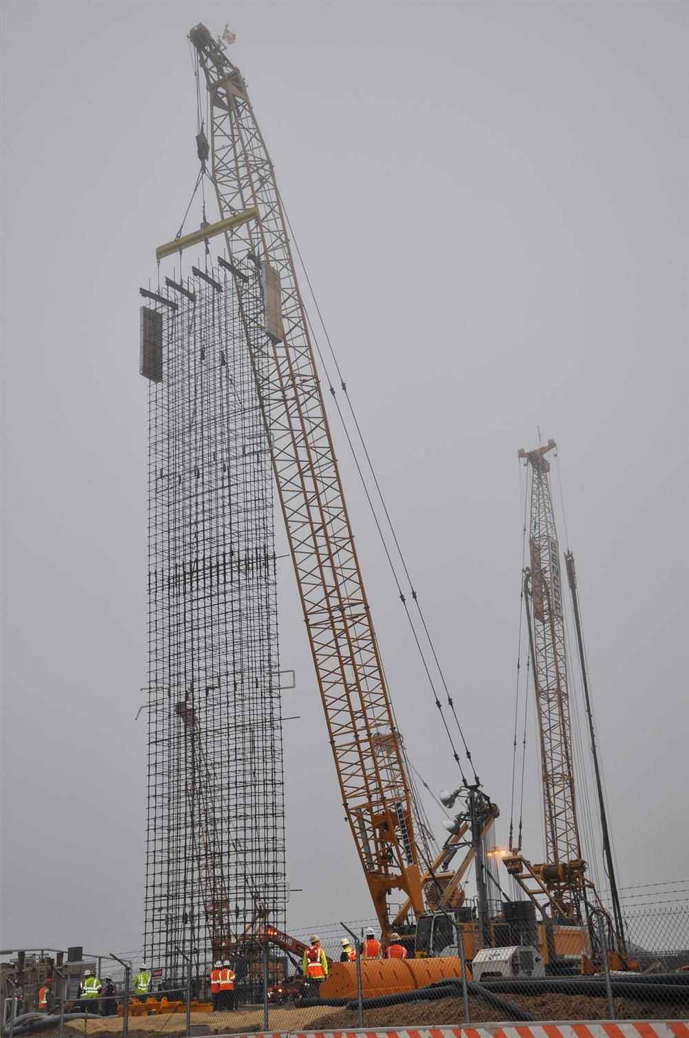 (DC Water photo) In preparation for excavating the main shaft on Blue Plains, steel cages are assembled and lowered into pre-dug holes more than 100 ft. (30.5) below the surface. Once concrete is poured, this reinforced structure will provide stability t