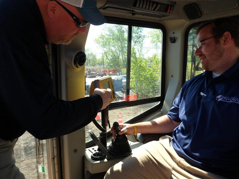 Rolf Witt (L), sales manager of Admar Supply, goes over the finer points of the Topcon GX60 with Evan Spencer, also of Admar Supply.