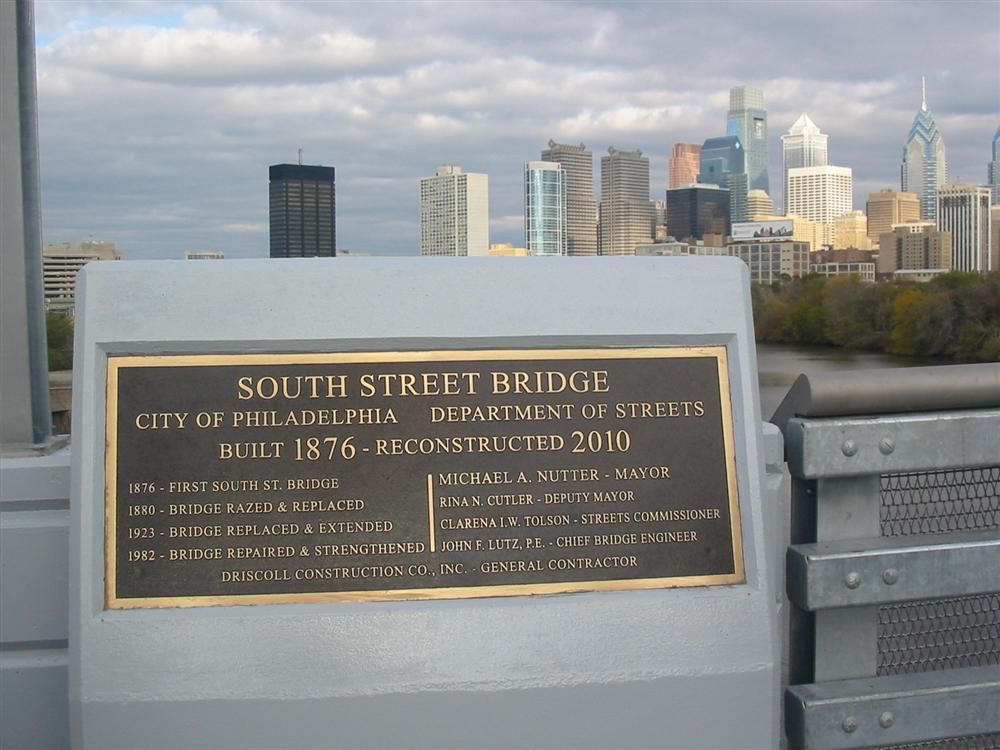 A plaque commemorating the reconstruction and building history of the South Street Bridge sits on the pedestrian sidewalk on the north side of the bridge.