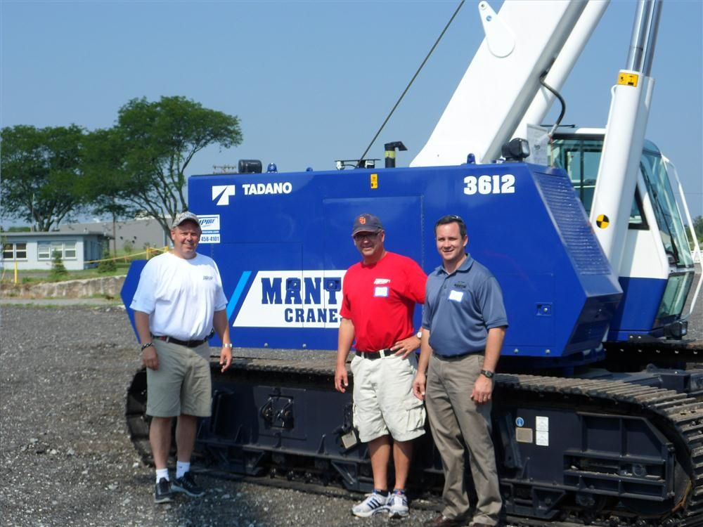 (L-R): Paul and Luke Lonergan, owners of Empire Crane, posed with Ed Hisrich, VP of Mantis Cranes, in front of a Mantis 3612.