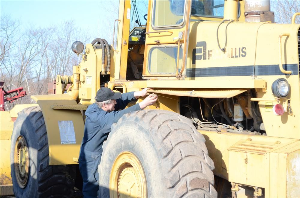 Ray Radotavich of Charley's Frontier Service, Buffalo, N.Y., checks the oil of a 745 C Fiat-Allis wheel loader.
