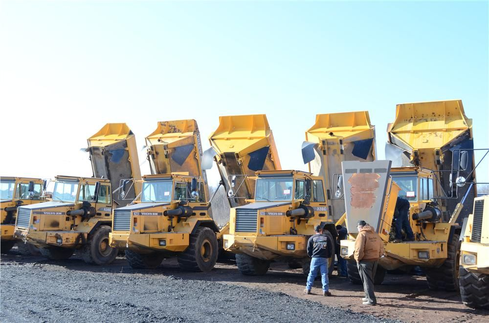 Bidders inspect the engines of several dump trucks prior to the start of the auction.