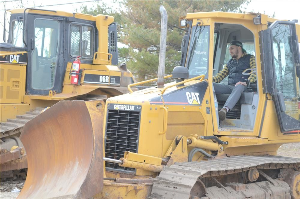 Marco Delia, owner of Delia Equipment Corp., West Chester County, N.Y., tries this Caterpillar dozer on for size.