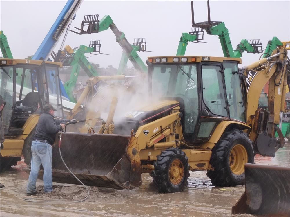 Last-minute steam cleaning is done before this Caterpillar backhoe is auctioned off.