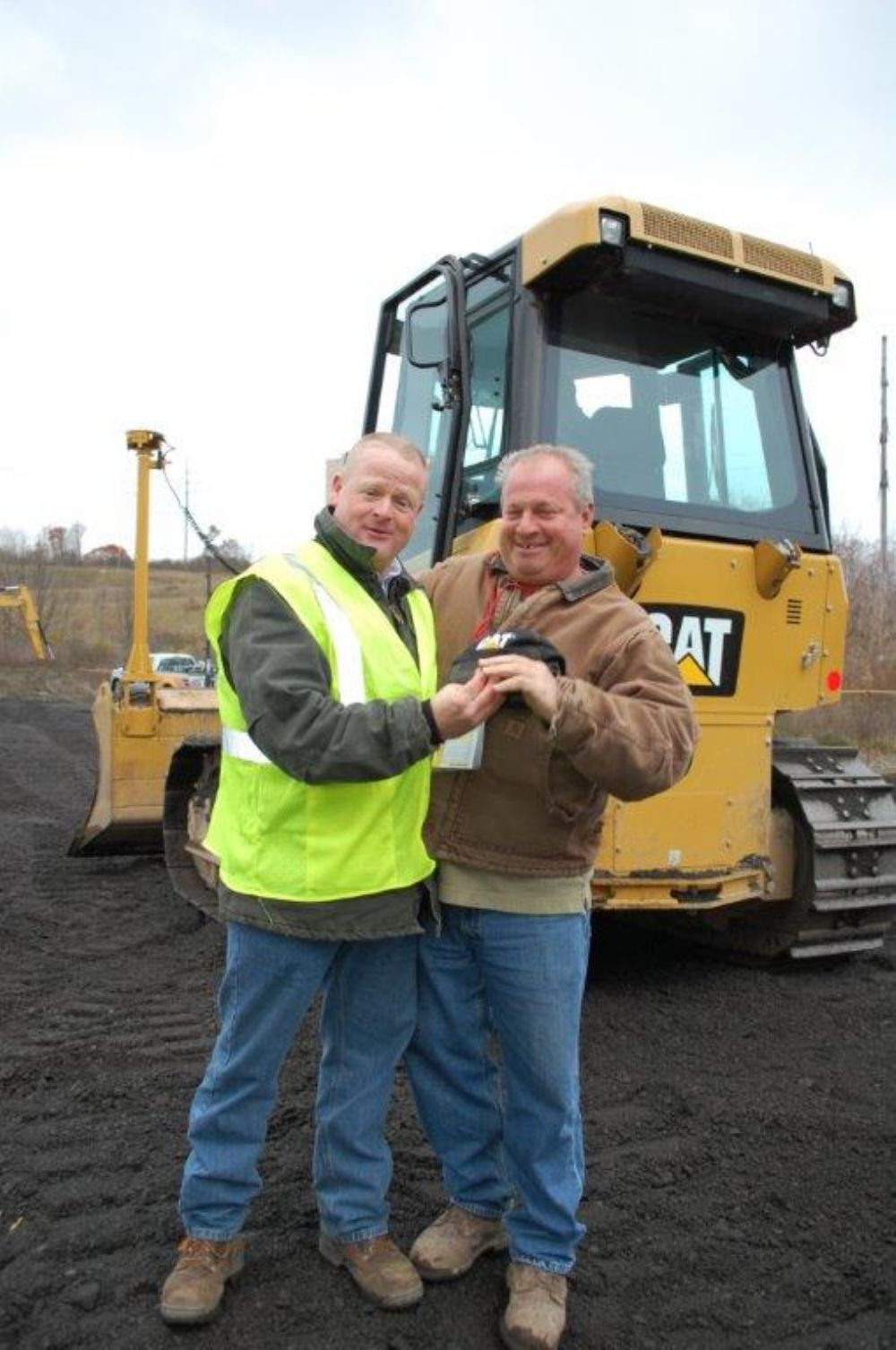 Gary Fisher (R) of Fisher Construction in Liverpool, N.Y., recently purchased one of these Cat D5 dozers equipped with Sitech technology. It's hard to tell which he is more excited about, the dozer or the complementary Cat hat he received from his M