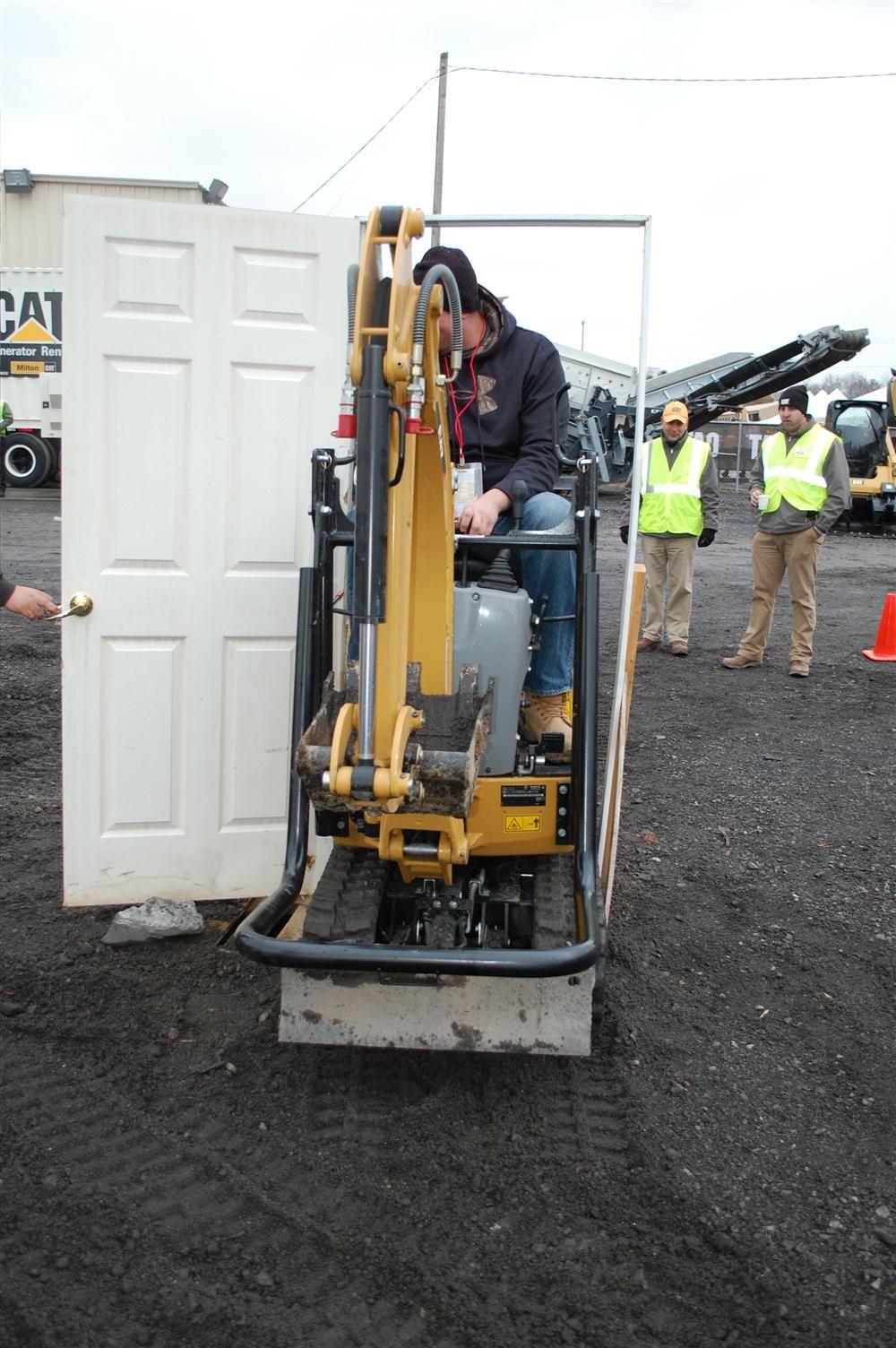 Nick Zielinski of Zielinski Asphalt in Oriskany, N.Y., demonstrates his skills as an operator by driving the excavator through a doorway.