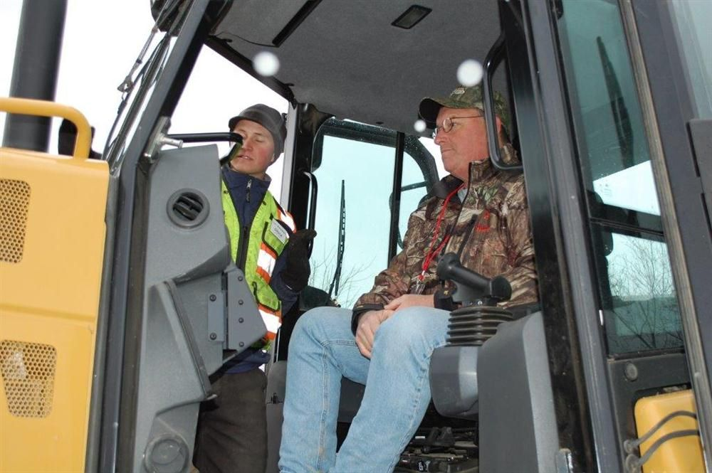 Phil Slocum (seated) of Slocum Development in Fulton, N.Y., is given the basic rundown on the laser grading technologies available through Sitech.