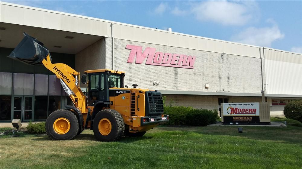 A Hyundai  HL750-9A wheel loader is proudly parked in front of Modern's building.