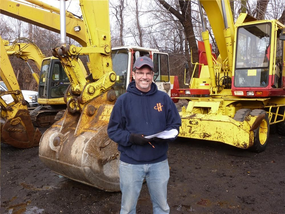 Harry Rice, account manager of Binder Machinery Company, records prices on the hydraulic excavators.