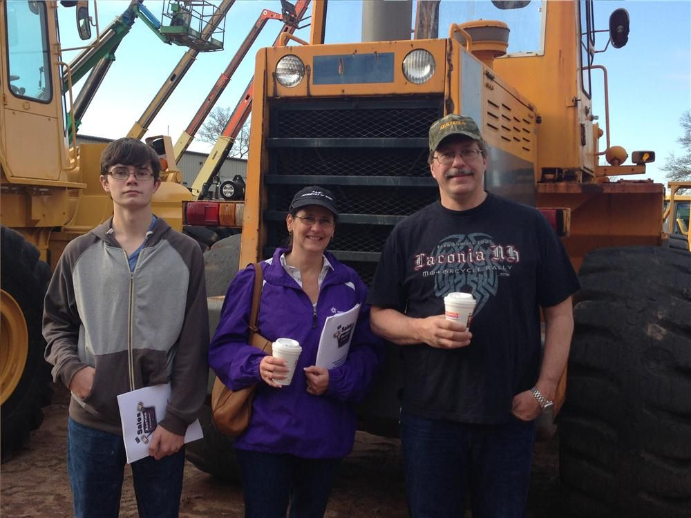 (L-R): Brad Webster, Denise Griffin and Mike Webster look at a wheel loader for their farm.