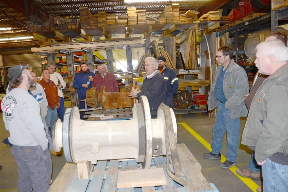 Whitney and Son Salesman Doug Baker (C) leads a group of students through the assembly of a cone crusher countershaft box.