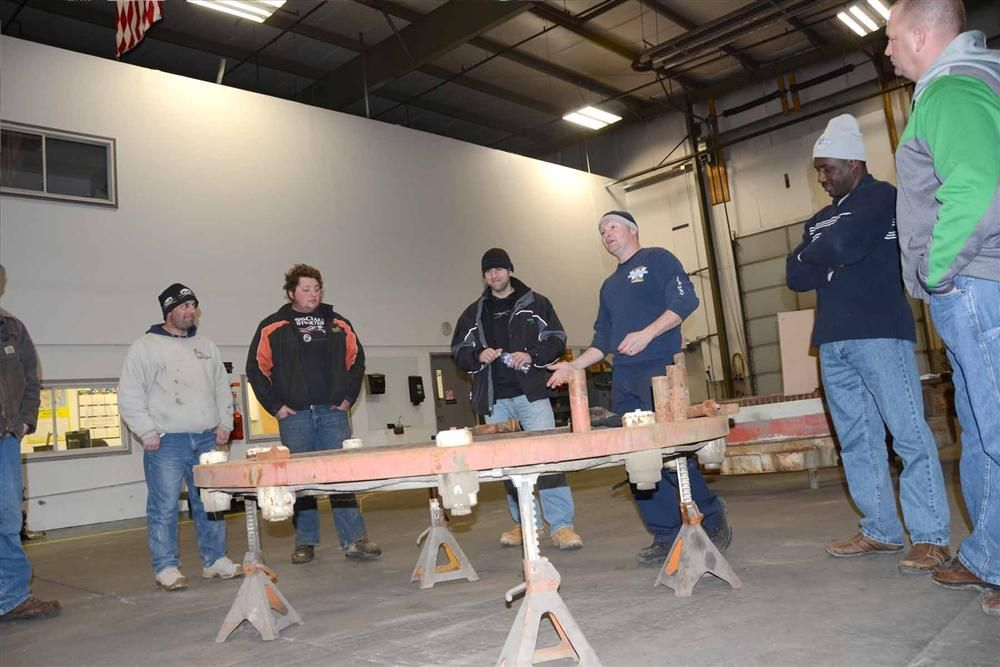(L-R): John Magnuson and Jeremy Castelli of New England Materials; Mike Vacciti of Aggregate Industries; Jamie Zisk; and Anthony Williams and Clay Newton of Century Aggregates discuss the assembly of the cone crusher clamp ring.