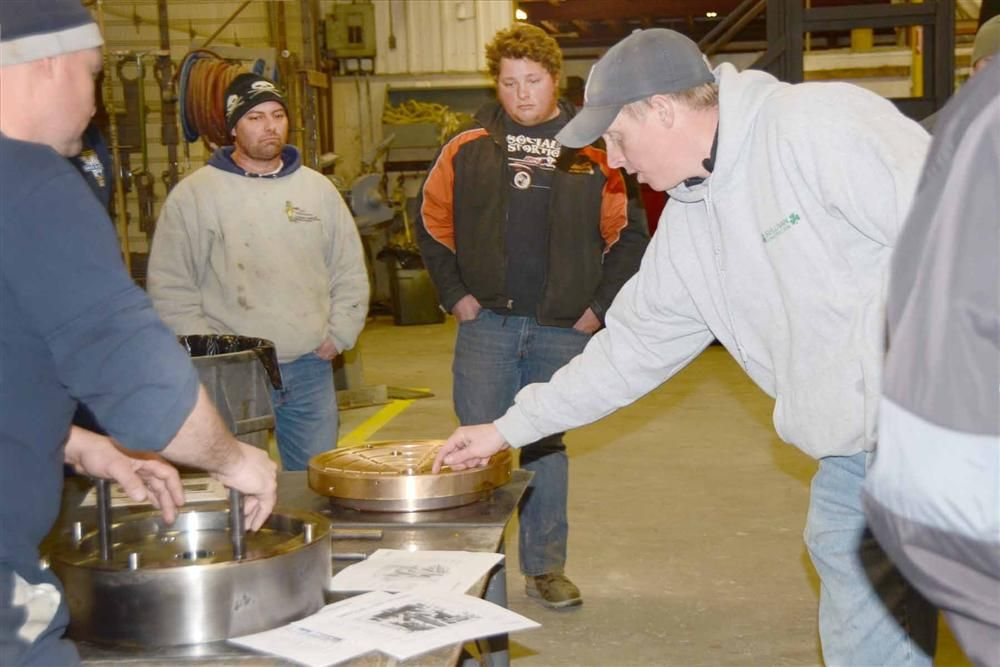 Jamie Zisk (L) and Tim Allard (R) of Benevento Sand and Stone discuss the socket liner from an HP300 cone crusher while John Magnuson (2nd from L) and Jeremy Castelli look.