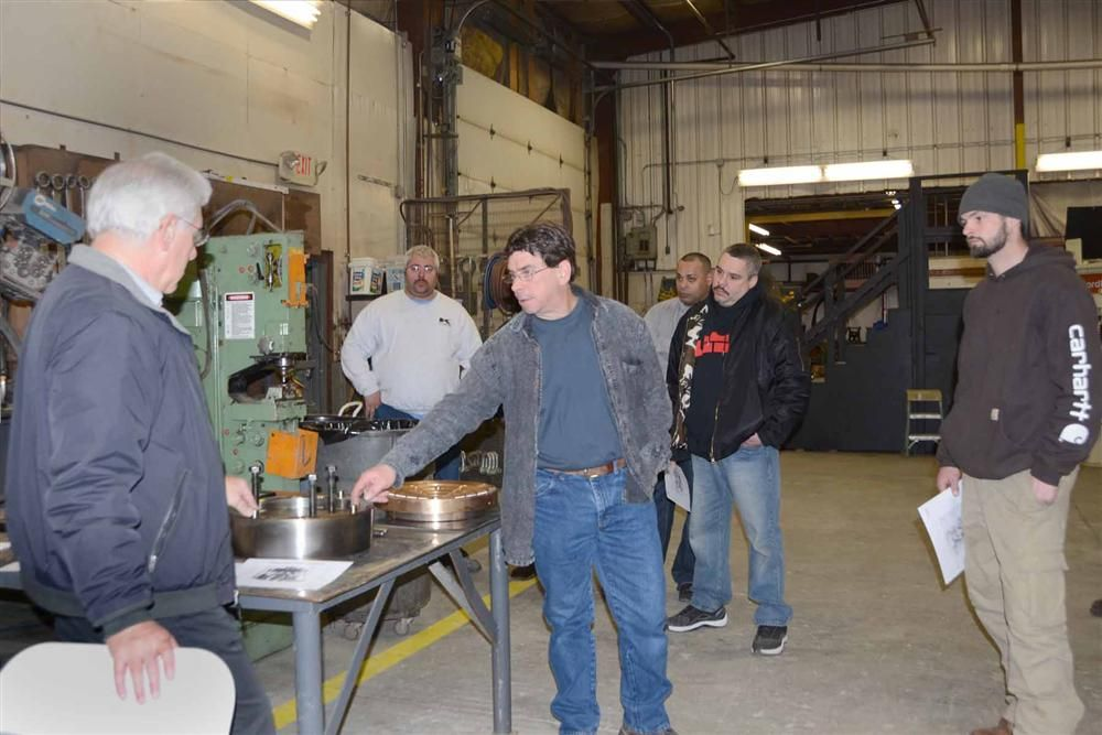 Doug Baker (L) and Dave Peters (C) of Tilcon CT discuss the installation of the socket on an HP300 while Jason Howd (R) and the rest of the crew from the Oldcastle Materials Group look on.