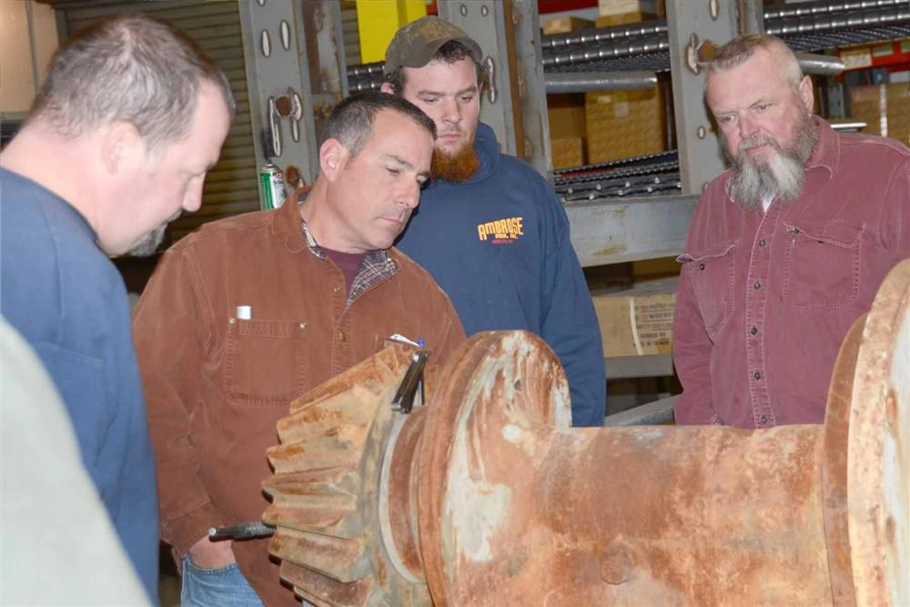 (L-R): Tim Belanger and Andy Deveno of John S Lane and Mike Frank and Kim Buker of Ambrose Brothers inspect the assembly of a cone crusher countershaft box.