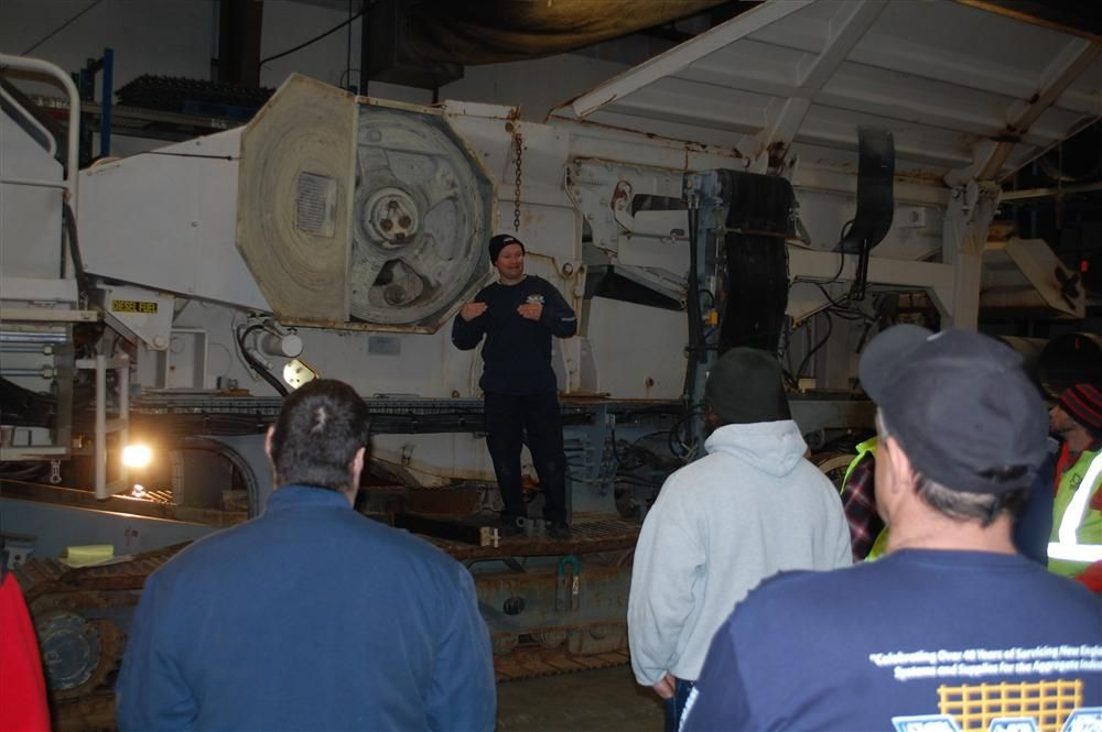 Whitney and Son Service Manager Jamie Zisk (C) explains jaw crusher flywheels to his group of guests.