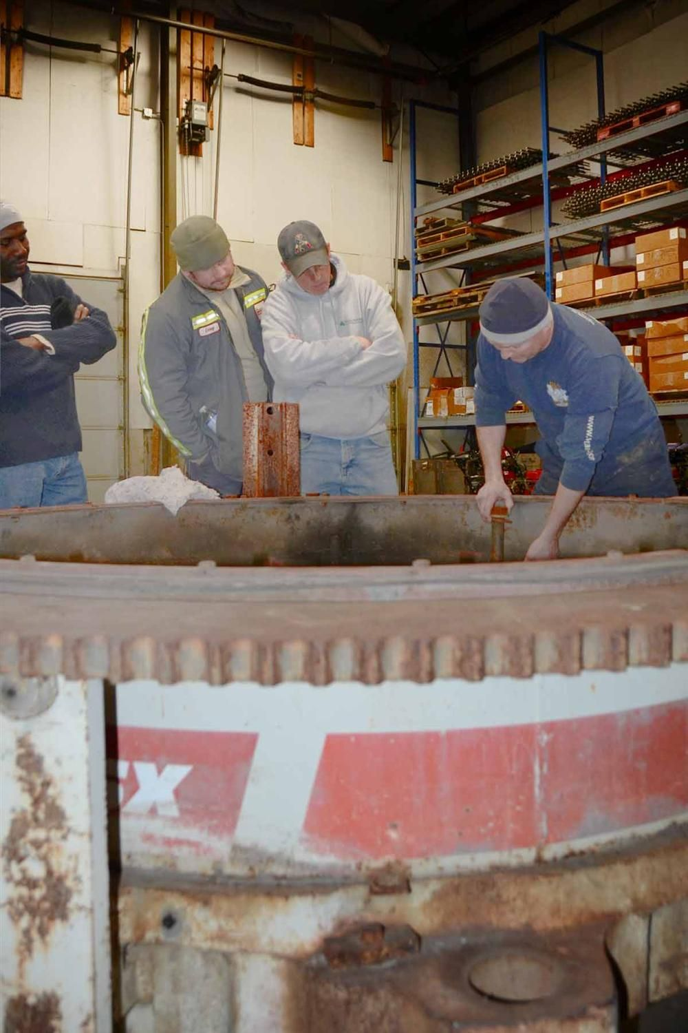 Jamie Zisk (R) demonstrates cone crusher clamp ring assembly to (L-R) Anthony Williams of Century Aggregates, and Tim Allard and Doug Pilcher of Benevento Sand and Stone.